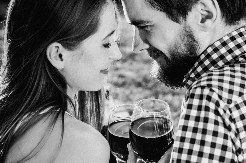 外国人カップルがワイングラスを持って見つめあう画像
