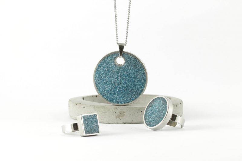 水色のネックレスと指輪が置いてある画像