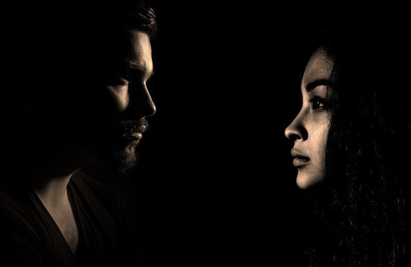 暗い画像で男女が正面を向き合っている画像