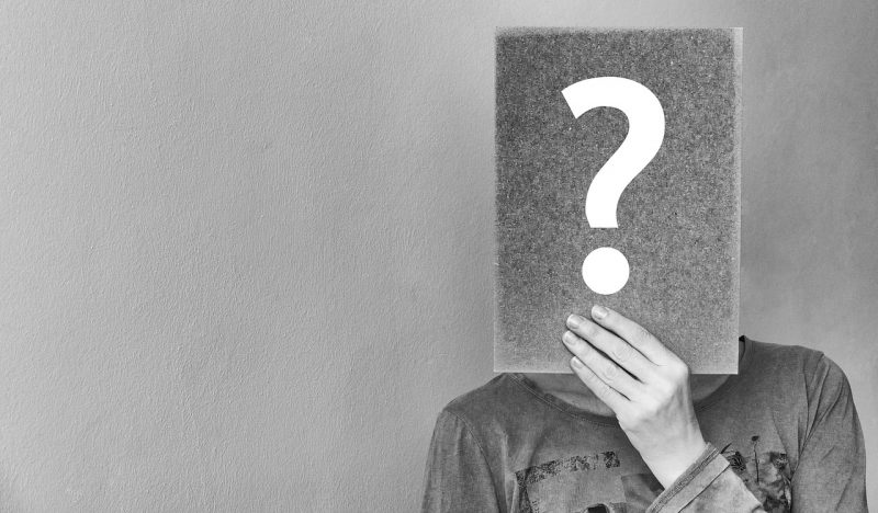 人が顔部分に「?」がかかれた紙を持って顔を隠している画像