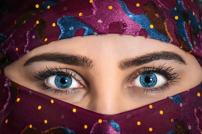 女性の顔が布に包まれていて目しか見えない画像