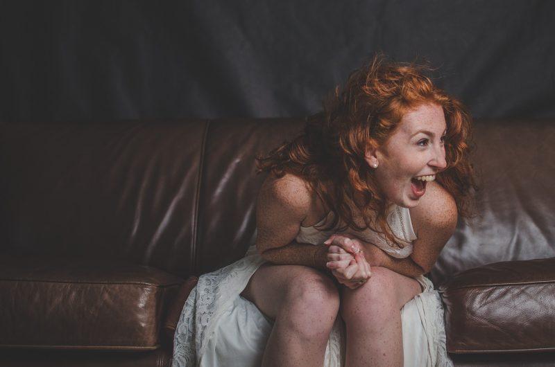 外国人女性がソファーに座って笑っている様子
