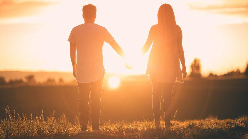 夕焼けを向いて男女が手を繋いでいる様子