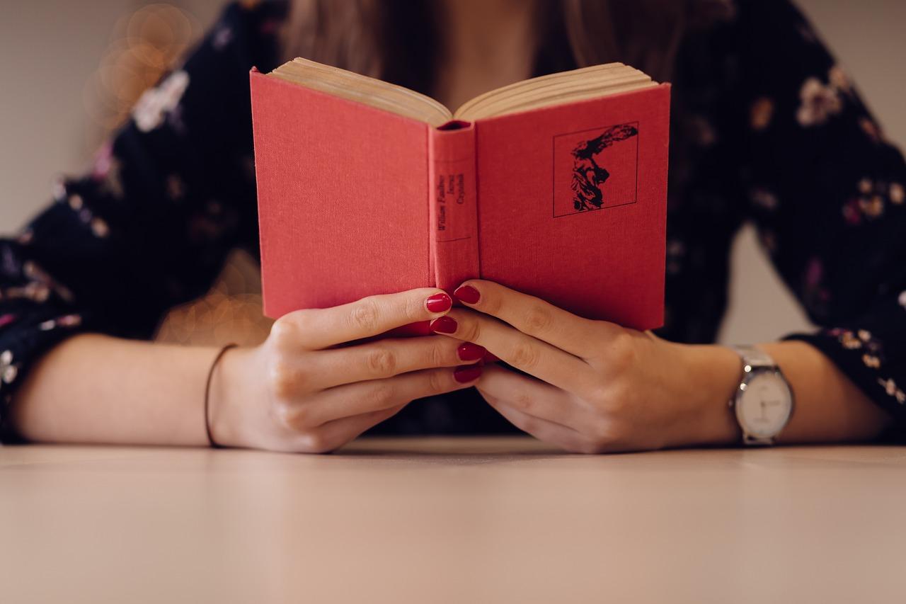 赤い本を読んで学んでいる女性