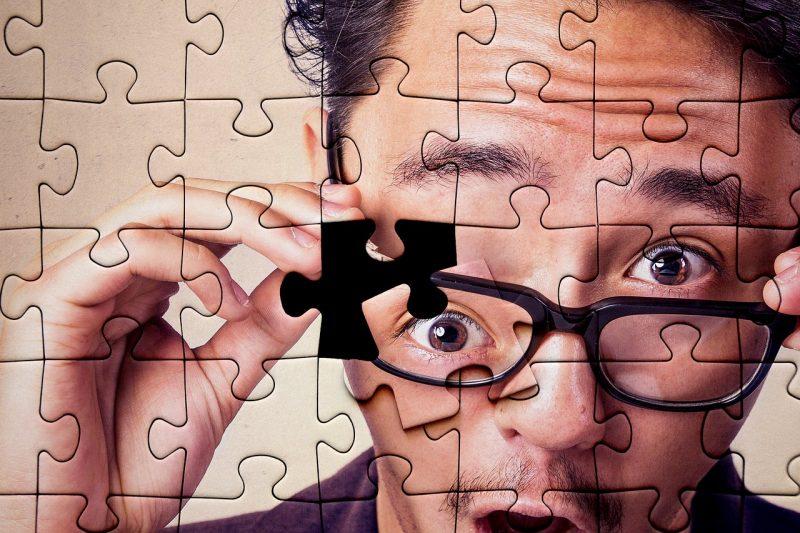 男性のジグソーパズルで目の部分が外れている画像
