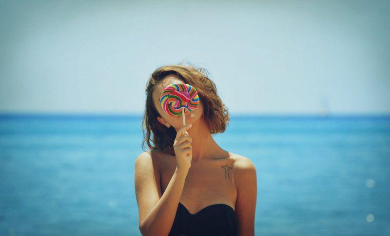 ビーチの女性が大きいキャンディーで顔を隠している画像