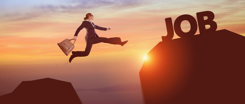 キャリアウーマンが崖を飛び超えいているイラスト