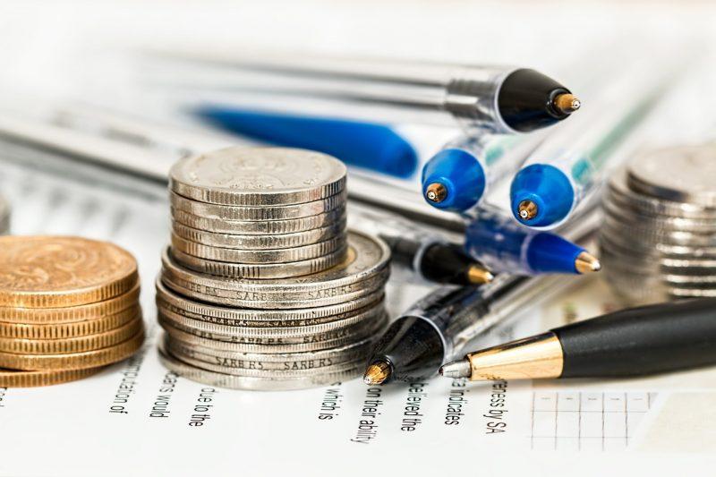 資料の上に置いてある硬貨とペンの画像