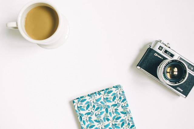 カメラとコーヒーと布が白いテーブルに置いてある