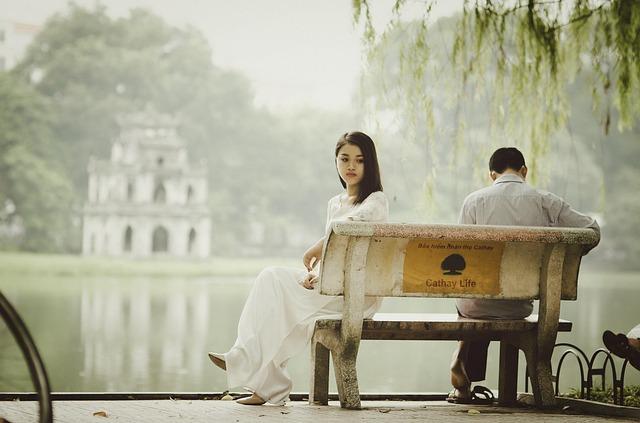 公園の池のベンチで男女が喧嘩して女性が違う方を向いている