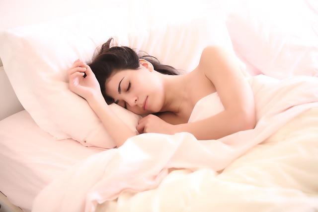 外国人女性が裸でベッドに横になっている
