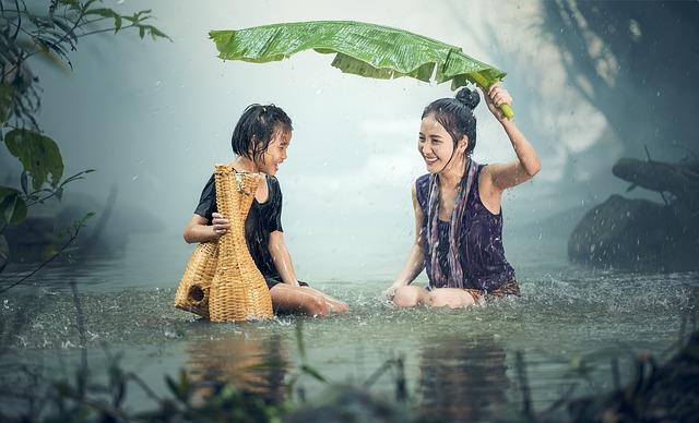 雨の中二人の女性が葉っぱを傘の代わりに使っている