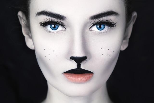 黒の背景に犬のような化粧をした青い目の女性