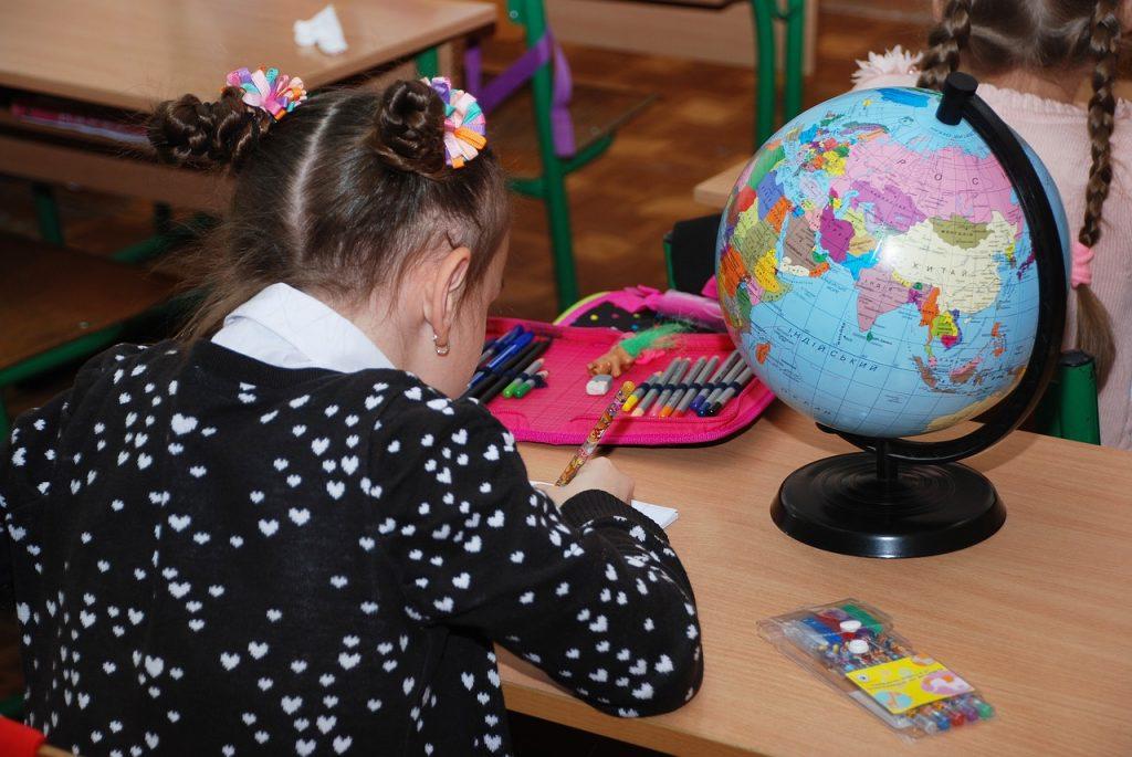 子供が地球儀の前で手紙を書いている様子