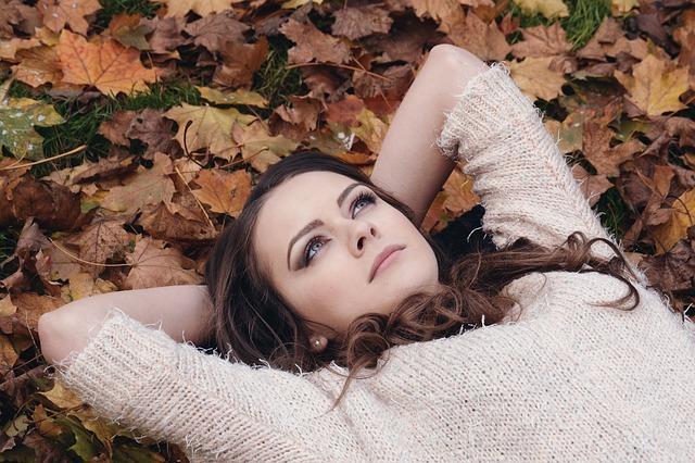 外国人の女性が木の葉の上で横になっている画像