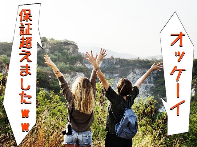 女性二人が山で両手を上げて喜んでいる