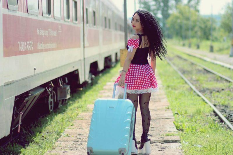 ピンクの服を着てキャリーケースを持った女性が線路を歩いている