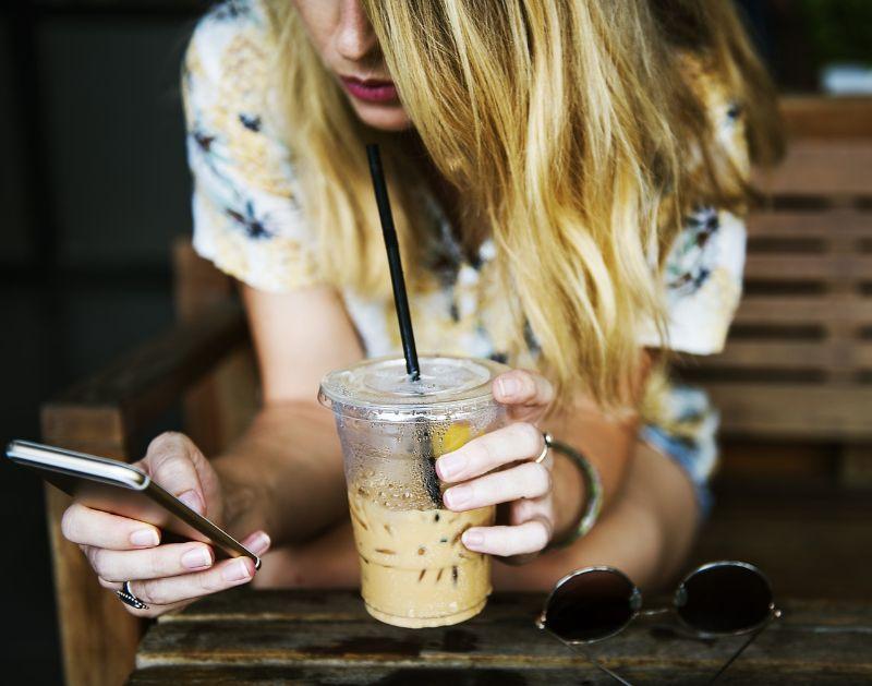 外国人女性がコーヒーを片手にスマホをいじっている画像