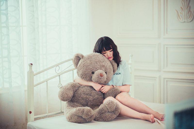 ベッドの上で女性が熊のぬいぐるみを抱いている様子