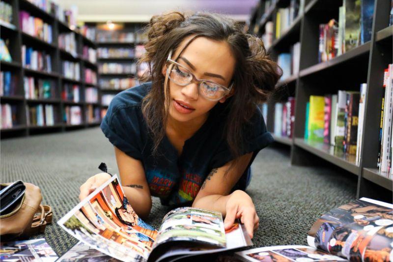 図書館で眼鏡をかけた女性が寝転んで本を読んでいる