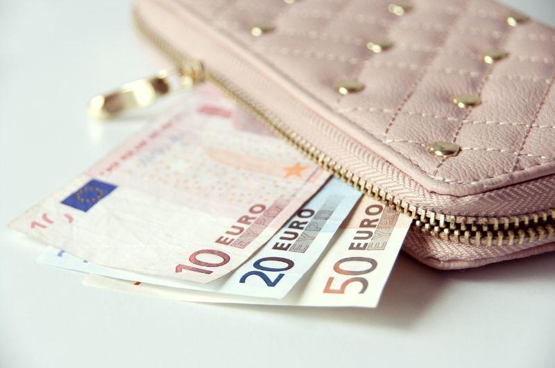 ピンクの財布からお金が飛び出している