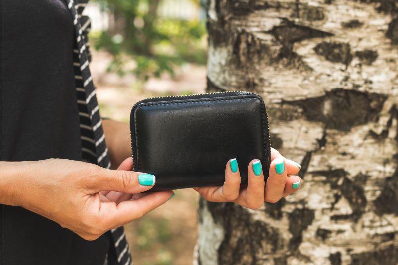 水色の爪をした女性が黒い財布を持っている画像