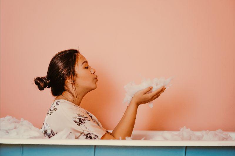 服を着た女性が泡風呂にはいっている画像