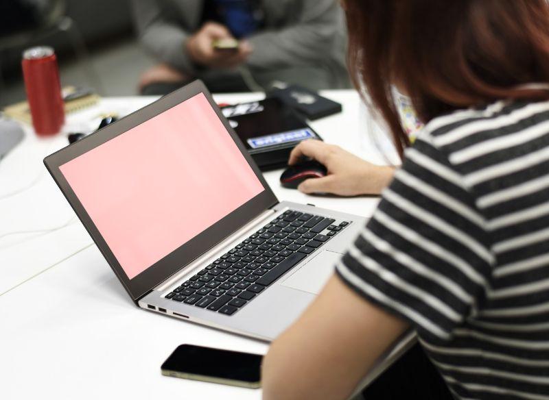 白黒の服を着た女性がパソコンを触っている画像