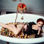 女性が服を着たままバスタブに浸かっている画像