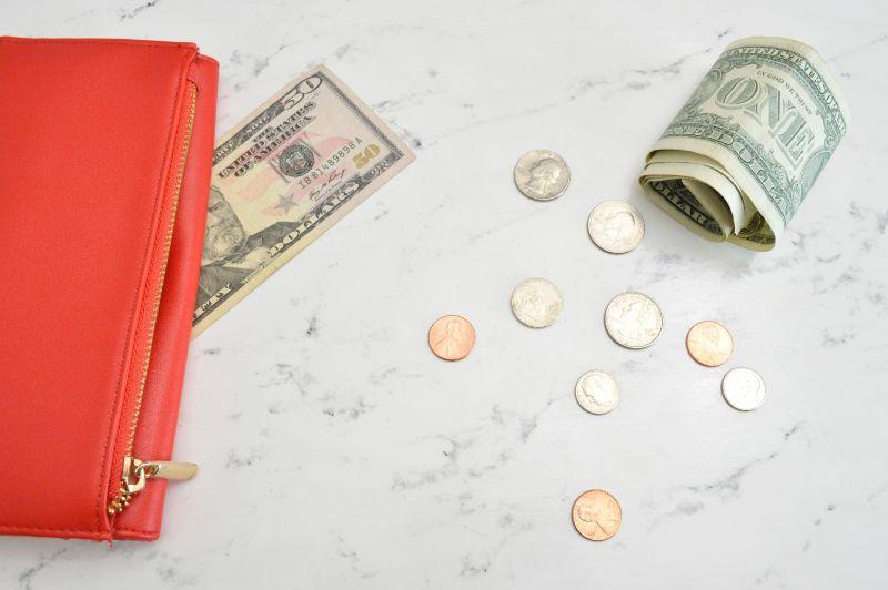 大理石の上の赤い財布とアメリカドル