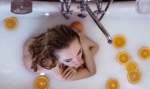 女性がオレンジと一緒にバスタブに入っている画像