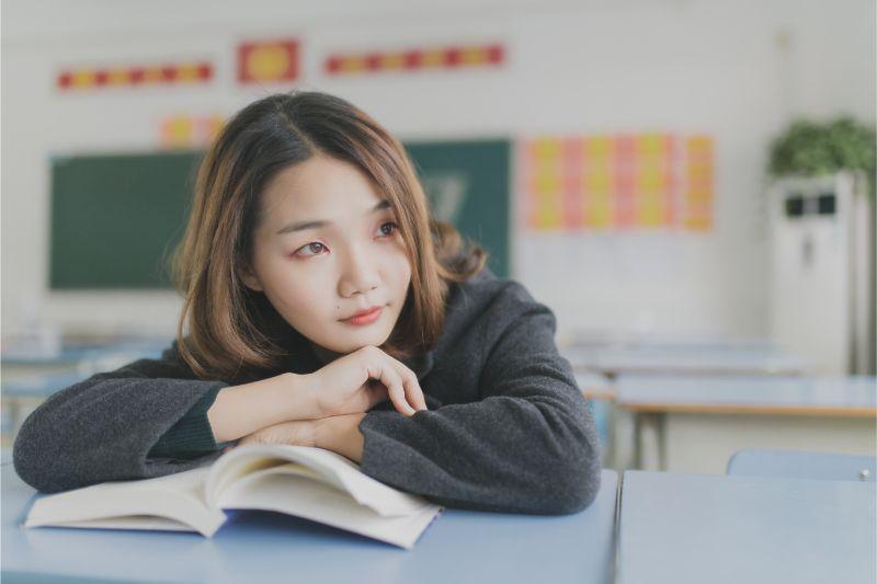 女性が本を開いて横を向いている画像