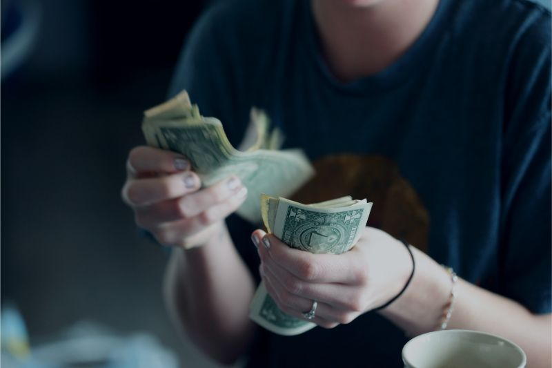 人がお金の札束を数えている画像