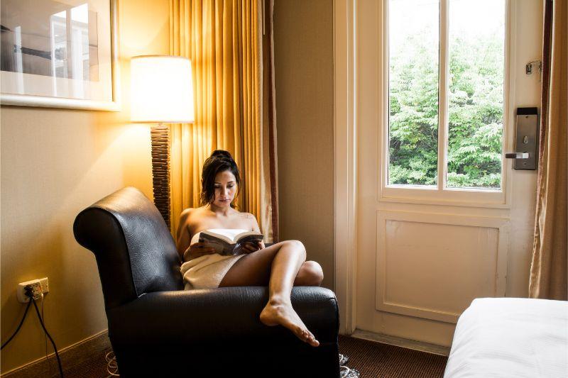 タオルをかけた女性が読書している画像