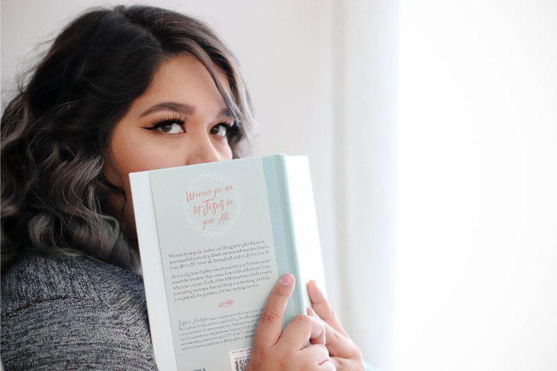 女性が本を顔に当てている画像