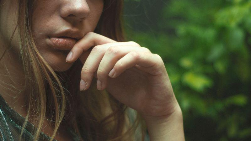 女性が口元に手を当てている画像