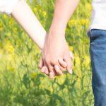 女性と男性が手を繋いでいる写真