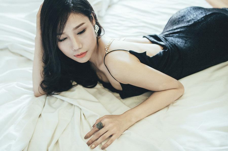 白いベッドに寝転がる黒い服を着た女性の画像