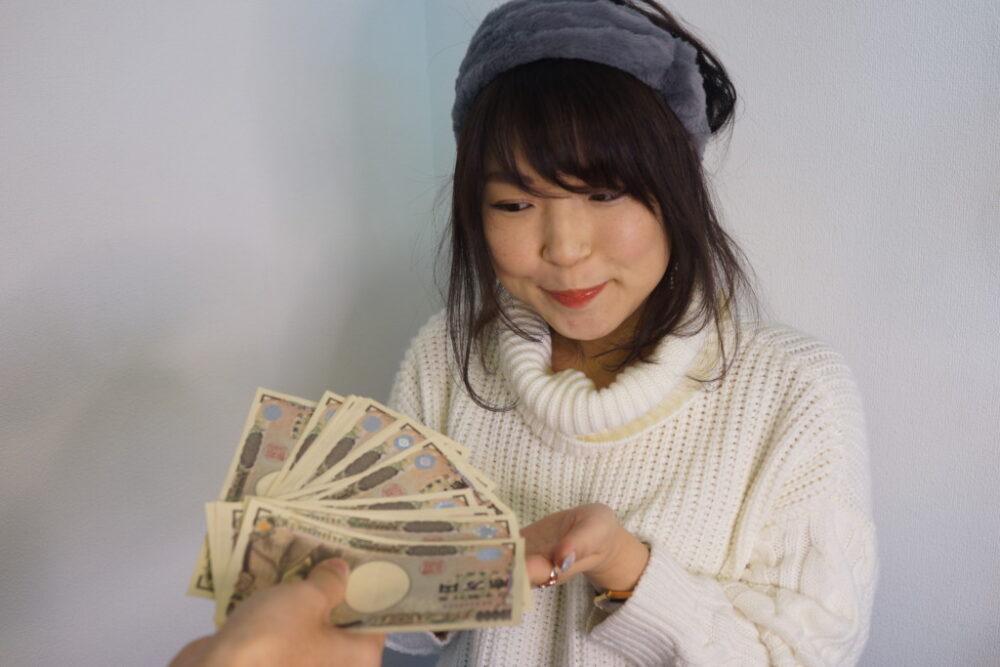 お札を手渡されて喜ぶ女性