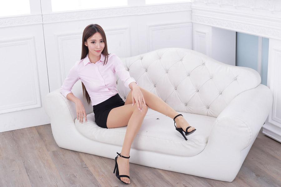 ソファに座るミニスカートの女性