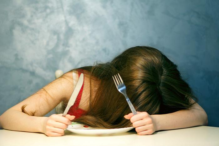 フォークとナイフを持ってテーブルに突っ伏す女性の画像