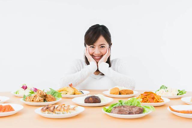 テーブル一杯に並んだ食事を前にして微笑む女性の画像
