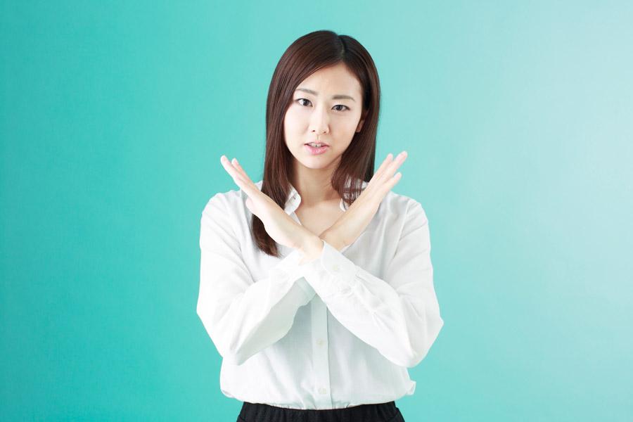 胸元でバツを作る若い女性の写真