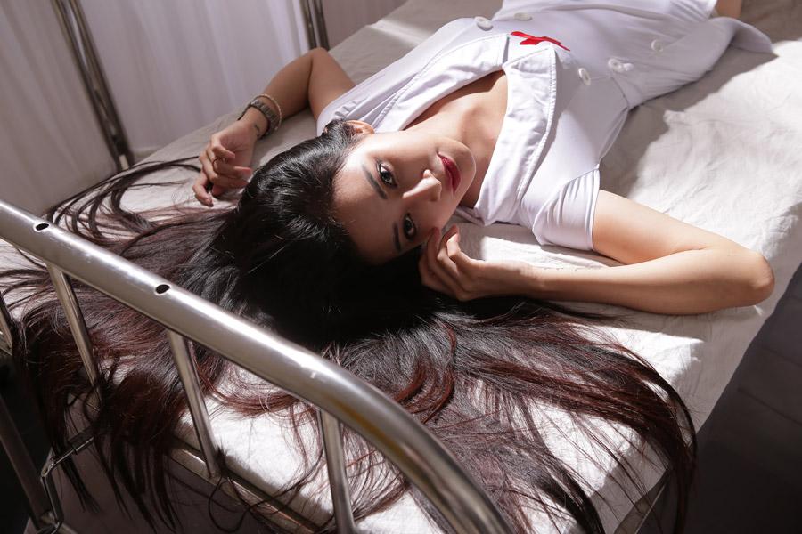 ナース姿でベッドに寝転ぶ若い女性の写真
