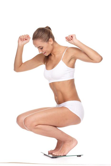体重計に乗って喜ぶ女性の写真