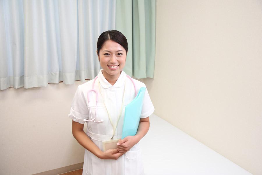 ファイルを脇に挟む看護婦の写真