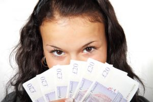 女性が外国紙幣を顔に当てている画像