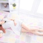 カラフルなベッドに女性が寝転がっている画像
