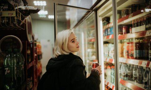 コンビニで食品を選ぶ女性の写真